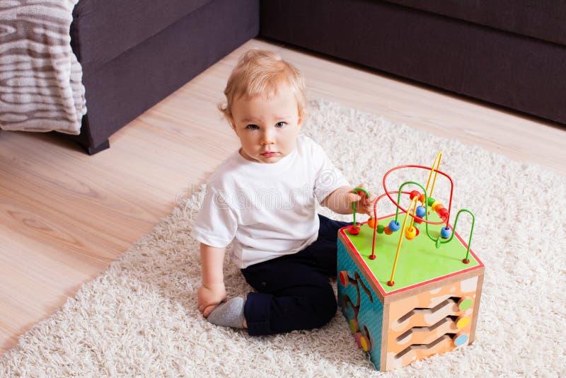 O menino esperto quer jogar com o brinquedo muito interessante imagem de stock