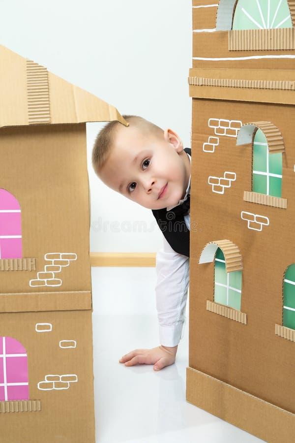 O menino espreita para fora atrás da casa do cartão fotos de stock royalty free