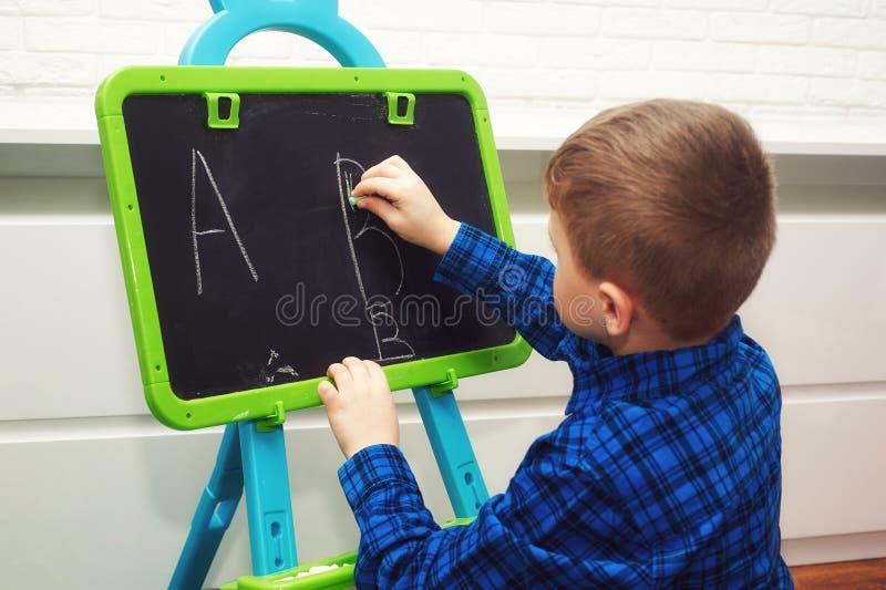 O menino está aprendendo ler e escrever A criança aprende o alfabeto fotos de stock royalty free