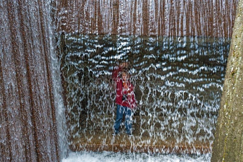 O menino está atrás da fonte da cachoeira foto de stock