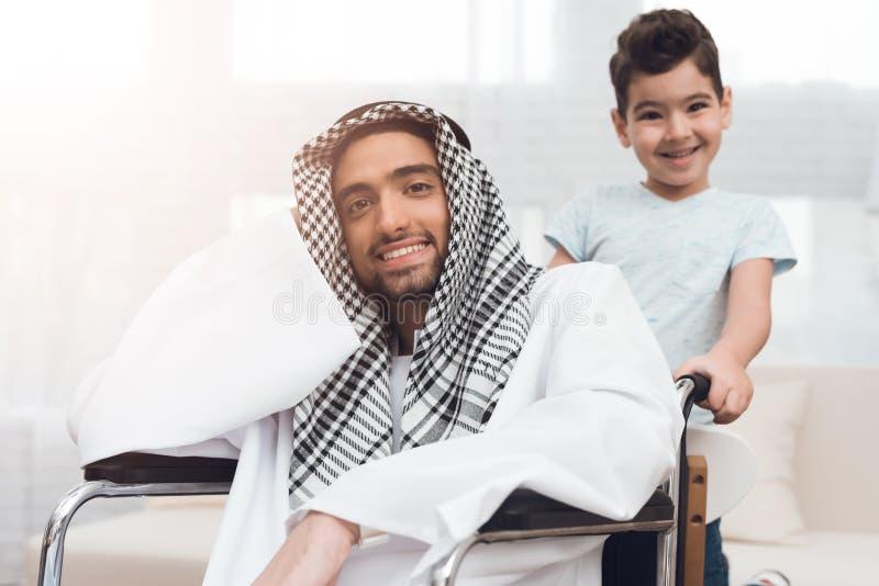 O menino está atrás do homem árabe em uma cadeira de rodas fotos de stock royalty free