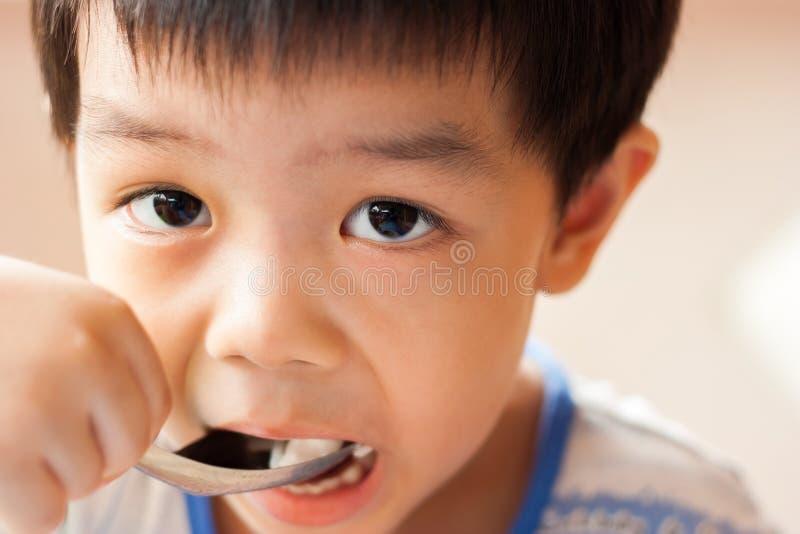 O menino está comendo imagem de stock royalty free