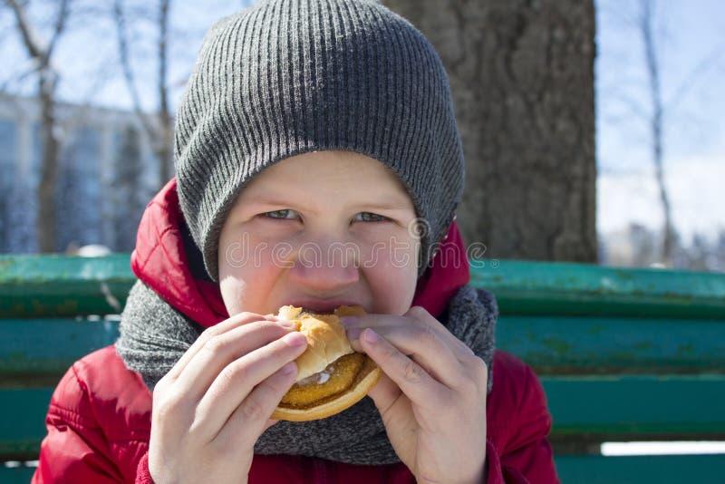 O menino está comendo o hamburguer exterior fotografia de stock