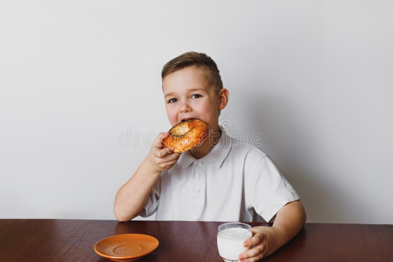 O menino está comendo um bagel e um leite da bebida foto de stock