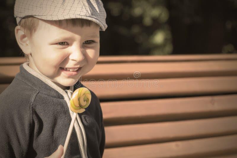 O menino está comendo um pirulito delicioso Um menino bonito lambe um pirulito foto de stock royalty free