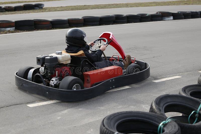 O menino está conduzindo vai-kart carro com velocidade em uma trilha de competência do campo de jogos foto de stock royalty free