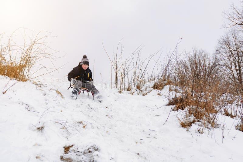 O menino está escondendo dos montes no trenó no parque imagem de stock
