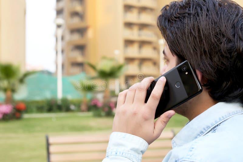 O menino está falando o telefone no parque imagem de stock