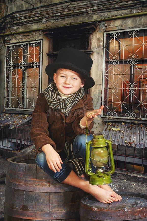 O menino está guardando uma lâmpada de querosene velha em suas mãos Retrato retro estilizado imagem de stock