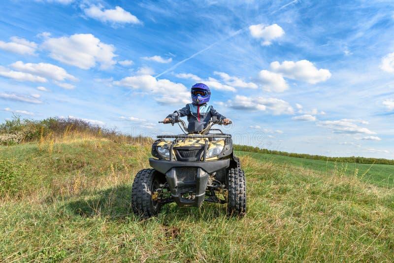 O menino está montando um ATV fora de estrada fotografia de stock royalty free