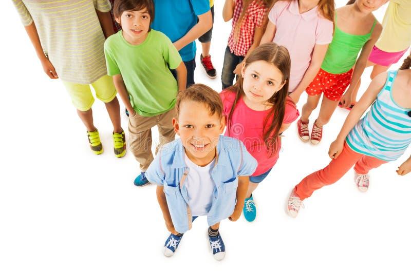 O menino está na frente do grande grupo das crianças de cima de fotografia de stock royalty free