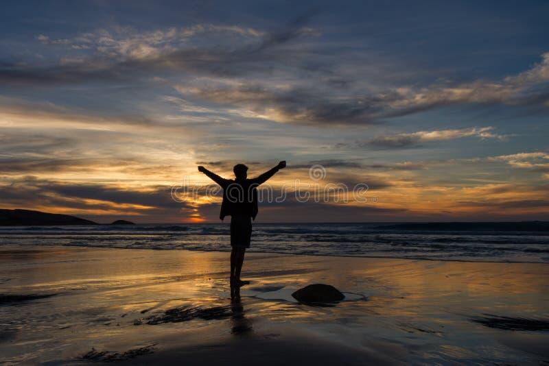 O menino está na praia com os braços estendido sob um céu dramático do por do sol imagens de stock royalty free