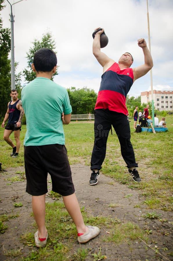 O menino está olhando aumentos do homem um o peso em uma competição amadora imagens de stock