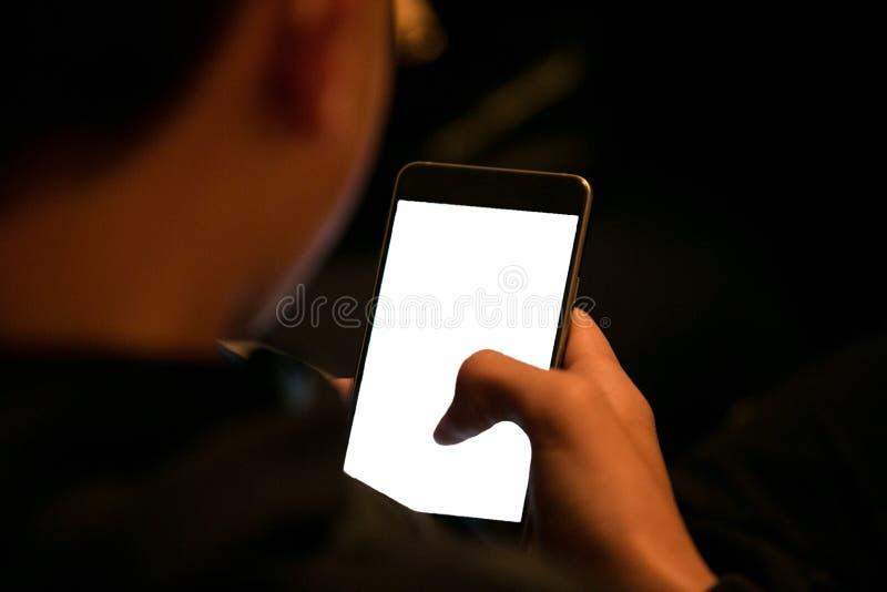 O menino está olhando o telefone imagens de stock