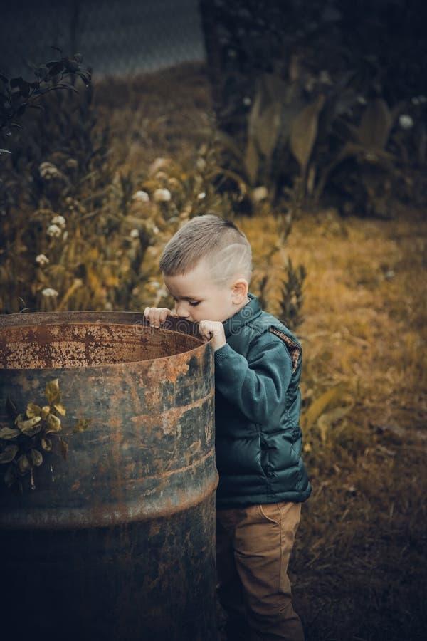 O menino está perto de um tambor vazio do metal oxidado imagens de stock royalty free