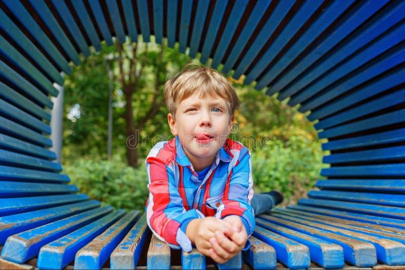 O menino está relaxando no campo de jogos durante o verão Criança que faz as caras engraçadas fotografia de stock