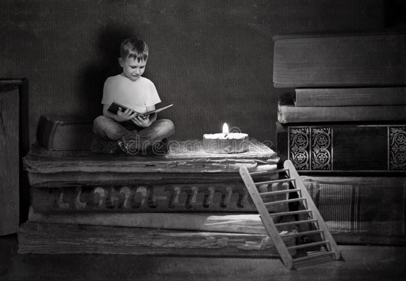 O menino est? sentando-se em livros grandes Uma escadaria de madeira conduz a uma pilha dos livros foto de stock royalty free