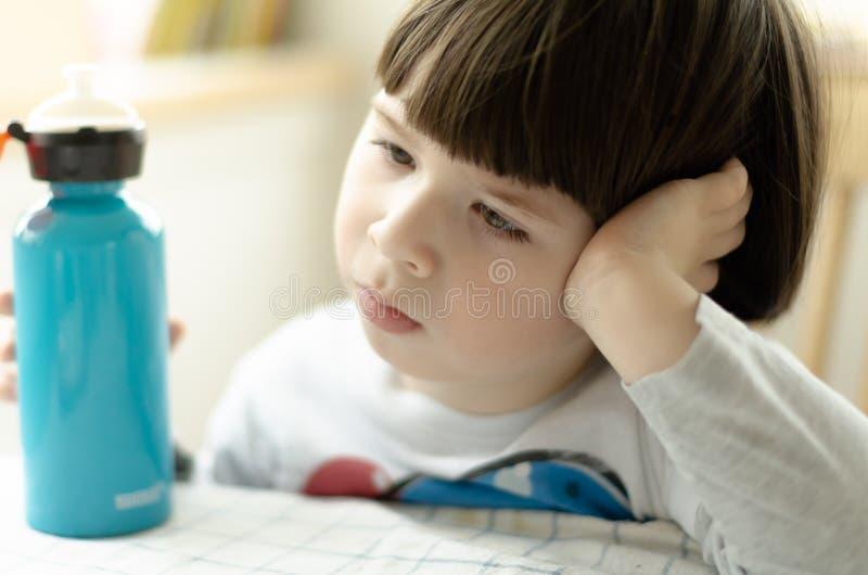 O menino está sentando-se na cadeira e está descansando-se sua cabeça em seus braço & x28; focus& raso x29; fotos de stock