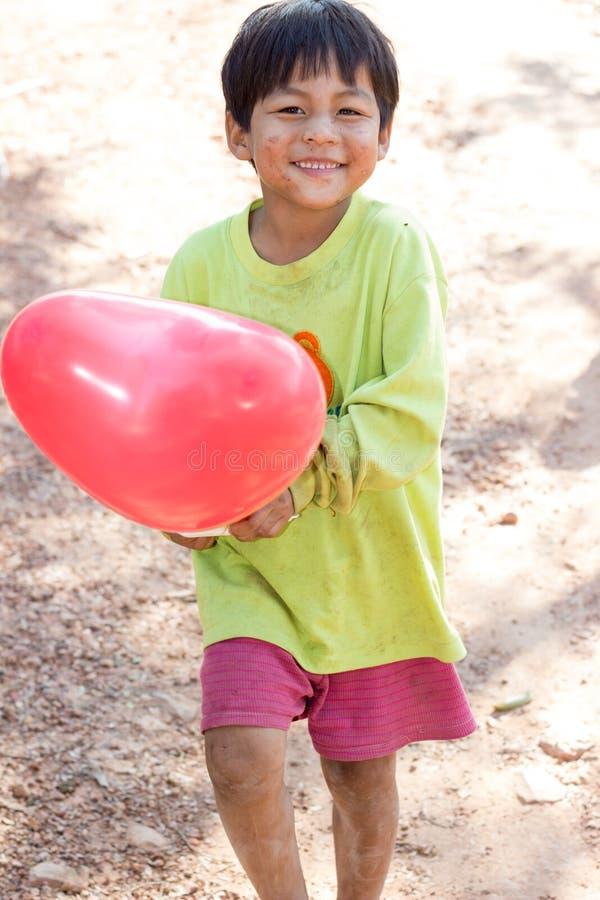 O menino está sorrindo na mão com um balão vermelho imagem de stock royalty free