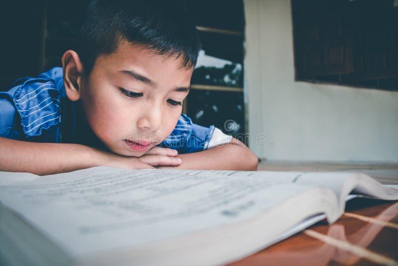 O menino est? lendo o livro para para preparar o exame nesta segunda-feira de vinda imagem de stock