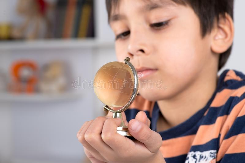 O menino estuda o globo fotos de stock royalty free