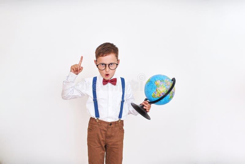 O menino exclama com seu dedo acima, guardando o globo em suas mãos veio acima com a ideia O come?o do ano escolar feliz imagens de stock royalty free