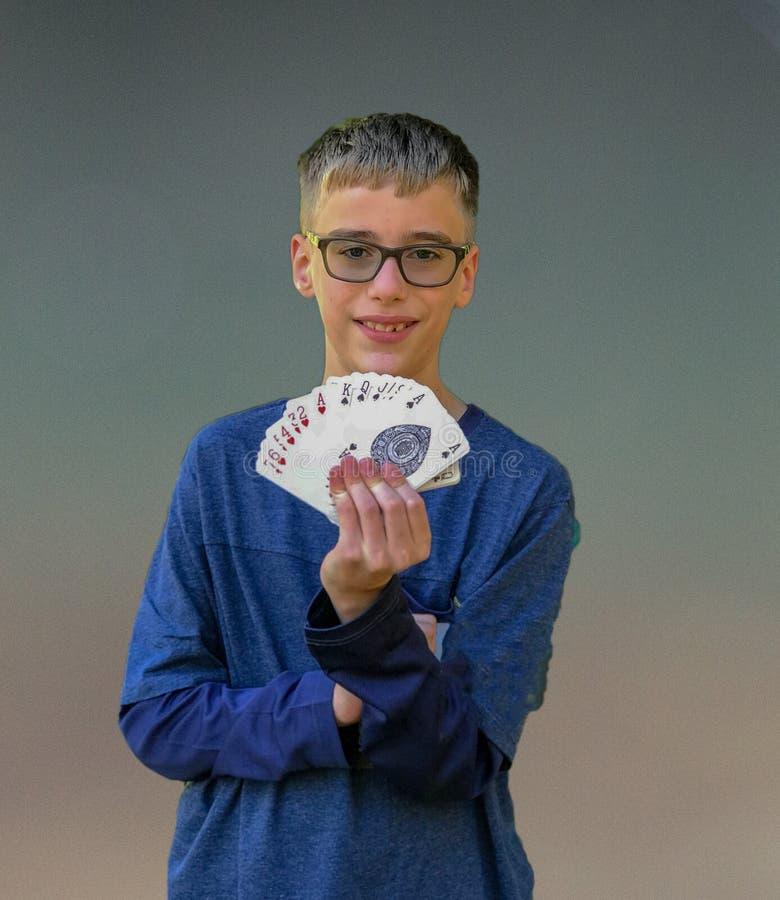 O menino executa o truque de cartão mágico foto de stock