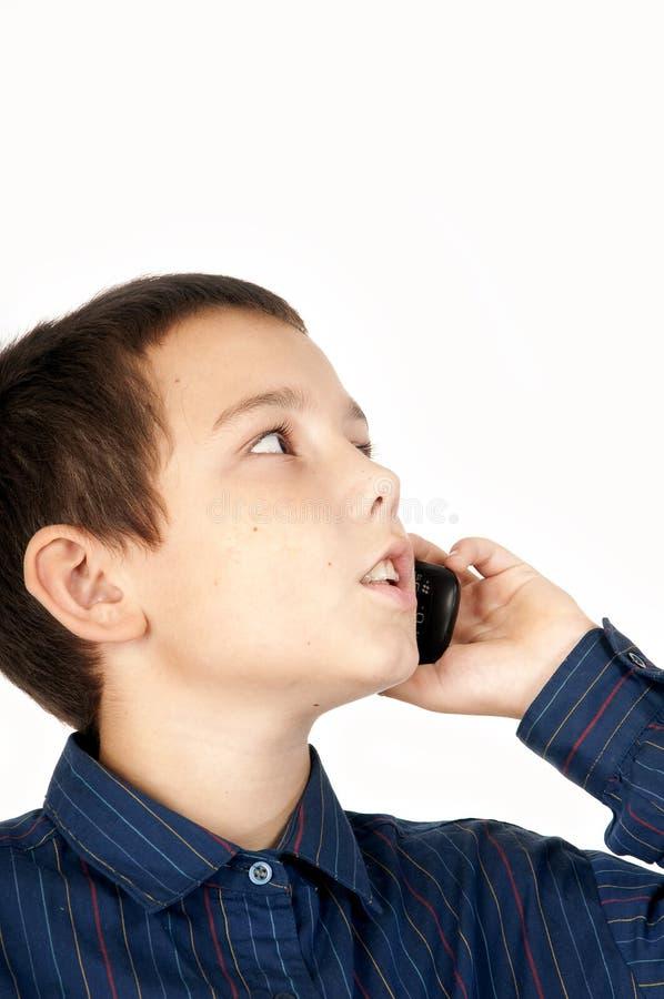 O menino fala por um telefone móvel imagem de stock