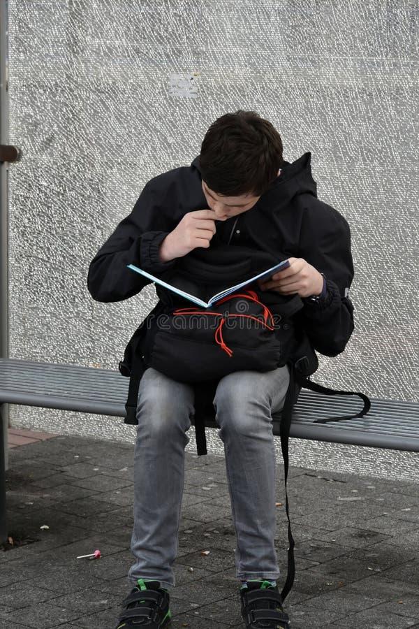 O menino faz trabalhos de casa da escola na parada do ônibus, ele aprende vocables fotografia de stock royalty free