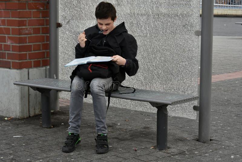 O menino faz trabalhos de casa da escola na parada do ônibus, ele olha irritado imagem de stock royalty free