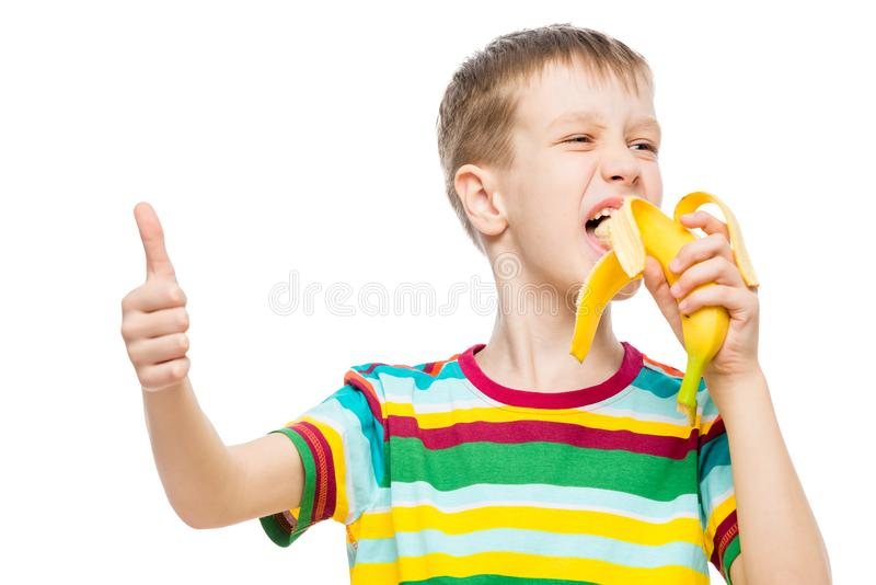 O menino feliz come a banana saboroso no fundo branco fotografia de stock
