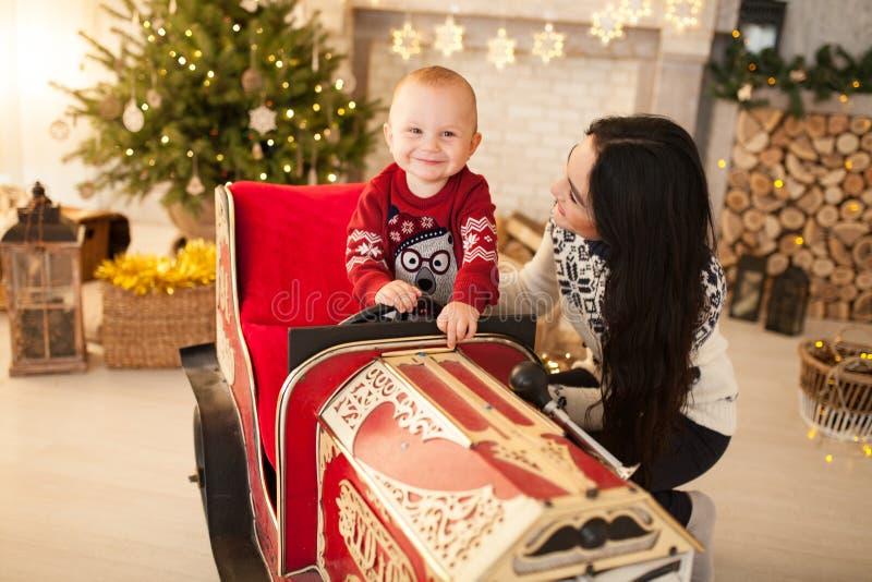 O menino feliz da criança está sentando-se no carro do brinquedo das crianças ao lado de sua mãe no fundo da árvore de Natal fotografia de stock