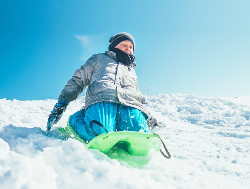 O menino feliz desliza para baixo do monte da neve usando o pequeno trenó OU do inverno imagem de stock