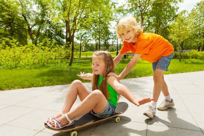 O menino feliz empurra a menina de sorriso com olhos fechados imagens de stock royalty free