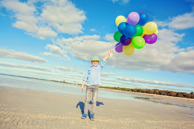 O menino feliz joga com os balões coloridos na praia fotos de stock