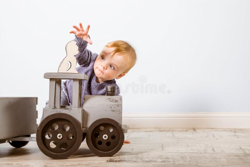 O menino feliz louro em uma camiseta azul senta-se em um assoalho de madeira Beb? de um ano que joga com brinquedos de madeira Qu imagens de stock