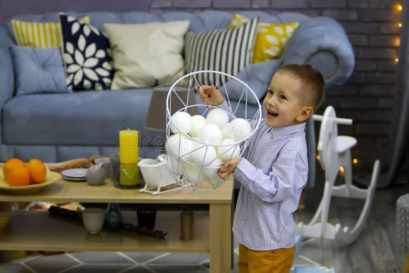 O menino feliz no Natal está jogando com a cesta com neve falsificada fotos de stock