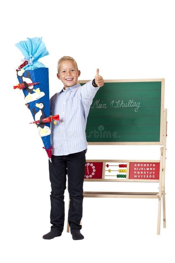 O menino feliz no primeiro dia de escola mostra o polegar acima foto de stock royalty free