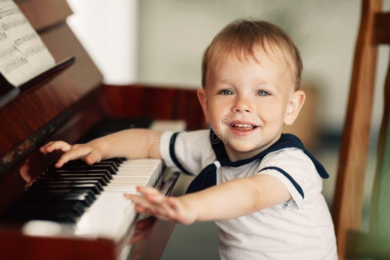 O menino feliz pequeno joga o piano fotos de stock royalty free