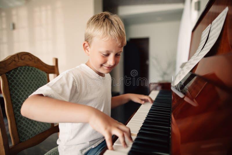 O menino feliz pequeno joga o piano imagem de stock