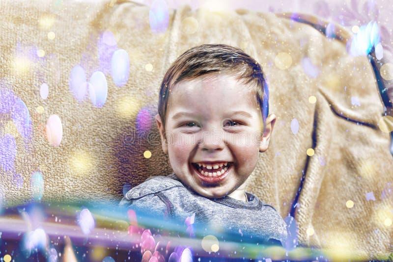 O menino feliz pequeno ri ao sentar-se no sofá em casa no interior do Natal imagens de stock