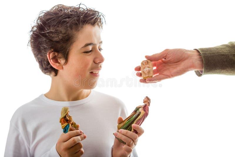 O menino feliz que guarda estátuas da ucha recebe a criança Jesus imagem de stock