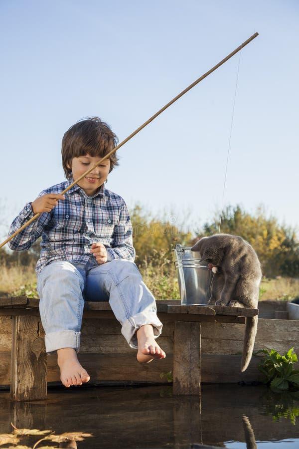 O menino feliz vai pescar no rio, um pescador das crianças com a foto de stock