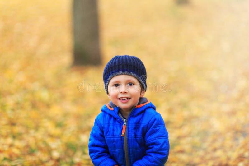 O menino feliz vestiu-se na roupa morna com chapéu e revestimento no colo azul imagem de stock royalty free