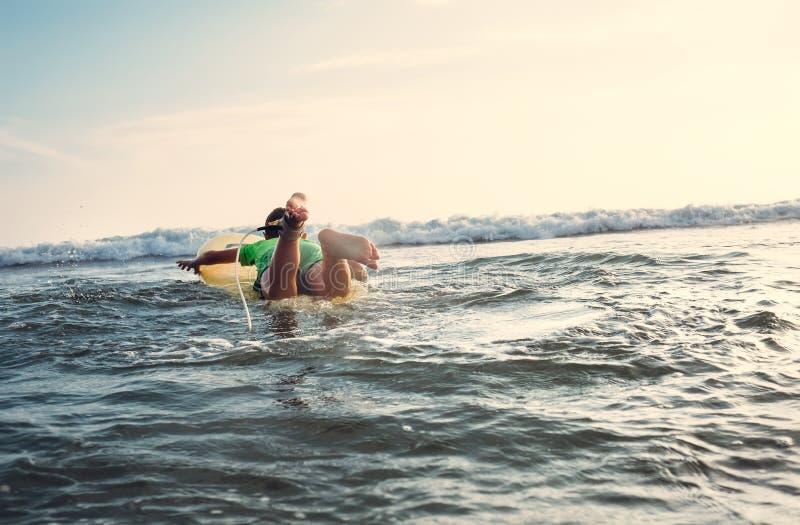 O menino flutua na placa de ressaca Surfista do novato, primeiras lições imagem de stock