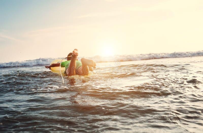 O menino flutua na placa de ressaca Surfista do novato, primeiras lições fotos de stock royalty free