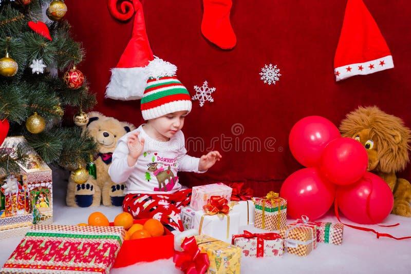 O menino foi deleitado com muitos presentes do Natal fotografia de stock