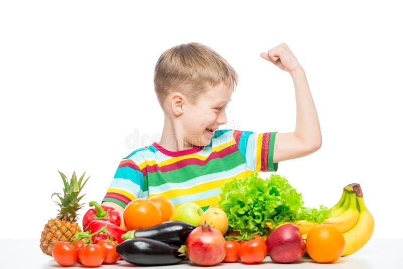 O menino forte mostra o bíceps na tabela com uma pilha de legumes frescos e de frutos isolados imagens de stock