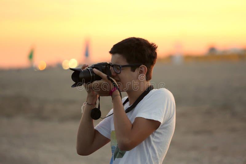 O menino fotografa o por do sol no mar fotos de stock