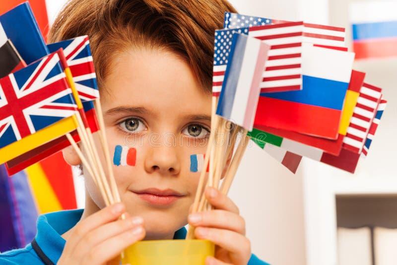O menino francês com a bandeira em mordentes esconde atrás das bandeiras fotos de stock royalty free